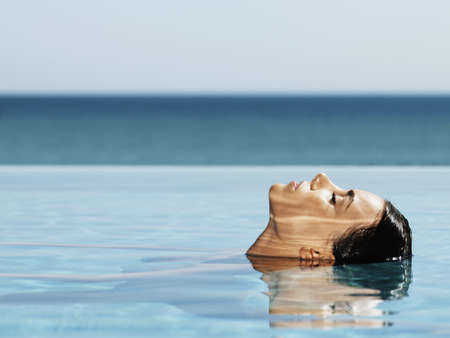 Hispanic woman in swimming pool LANG_EVOIMAGES