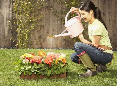 Asian woman watering flowers