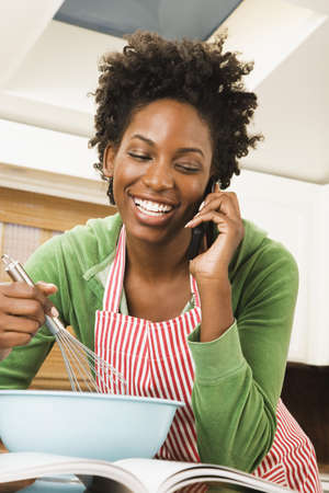 African American woman talking on cell phone and baking LANG_EVOIMAGES