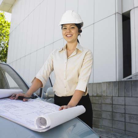 Eurasian businesswoman spreading blueprints on car