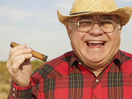 Senior Mixed Race man holding cigar LANG_EVOIMAGES