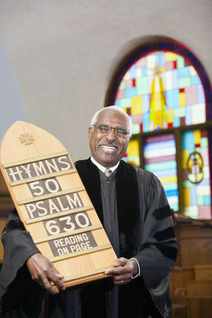 African Reverend holding hymn board