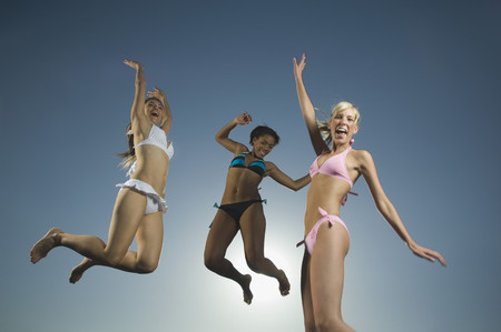 Multi-ethnic women in bathing suits jumping LANG_EVOIMAGES