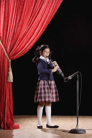Hispanic girl playing clarinet on stage LANG_EVOIMAGES