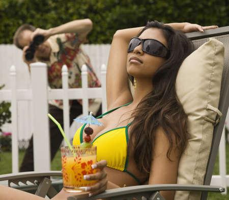 Man spying on Hispanic woman sunbathing LANG_EVOIMAGES