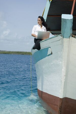 Hispanic businesswoman working on boat LANG_EVOIMAGES