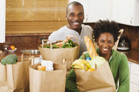 African American couple with groceries in kitchen