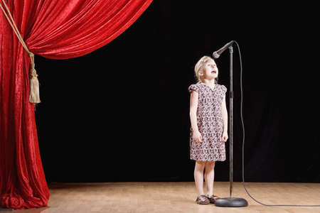 Girl speaking into microphone on stage LANG_EVOIMAGES