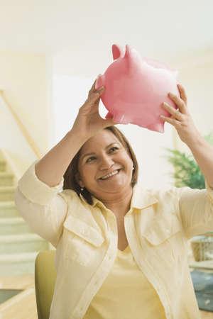 Hispanic woman holding up piggybank LANG_EVOIMAGES