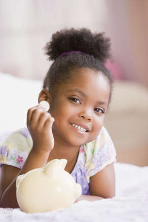African American girl putting coin in piggybank LANG_EVOIMAGES