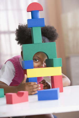 African American girl looking through block tower LANG_EVOIMAGES