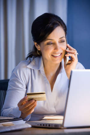 Hispanic businesswoman shopping online LANG_EVOIMAGES