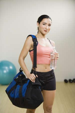 Hispanic woman holding gym bag