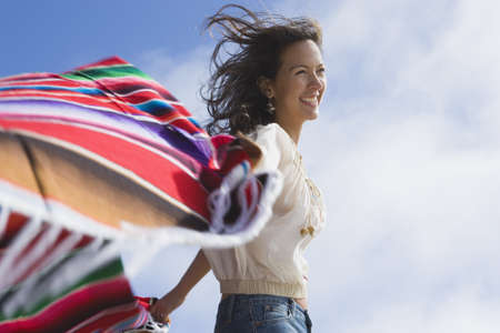 Hispanic woman holding blanket in wind