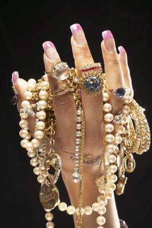 Indian woman's hand holding flashy jewels LANG_EVOIMAGES