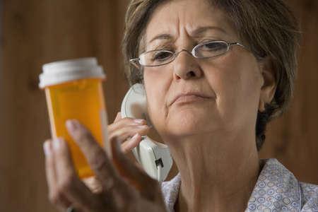 Senior Hispanic woman calling in prescription LANG_EVOIMAGES