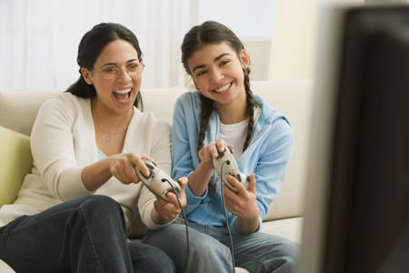 Hispanic mother and daughter playing video game