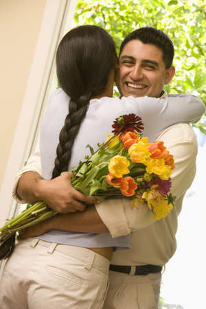 Hispanic couple hugging with flowers LANG_EVOIMAGES