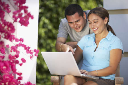 Multi-ethnic couple looking at laptop LANG_EVOIMAGES