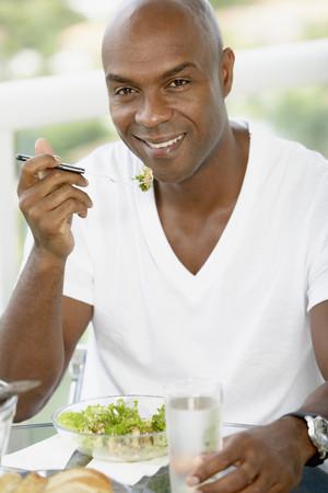 African American man eating salad LANG_EVOIMAGES