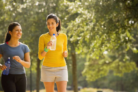 Hispanic women walking in park LANG_EVOIMAGES