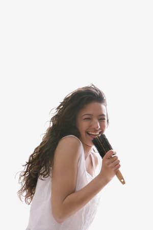 Hispanic teenaged girl singing into hairbrush