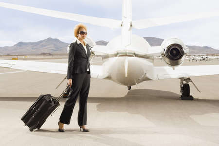 African American businesswoman pulling suitcase