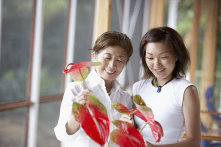 Asian mother and adult daughter arranging flowers