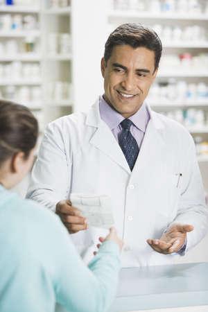 Hispanic male pharmacist handing prescription to customer LANG_EVOIMAGES