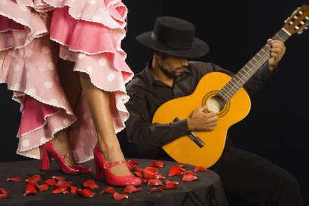 Hispanic female flamenco dancer next to guitar player LANG_EVOIMAGES