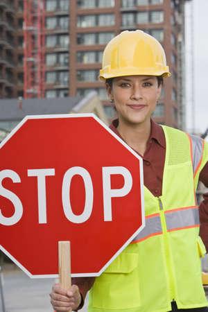 Hispanic female construction worker holding stop sign LANG_EVOIMAGES