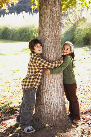 Mixed Race brother and sister hugging tree