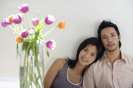Asian couple next to flowers in vase