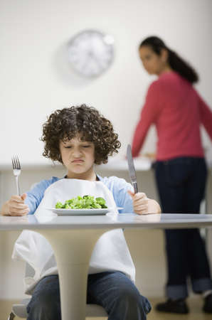 Hispanic boy making face at salad