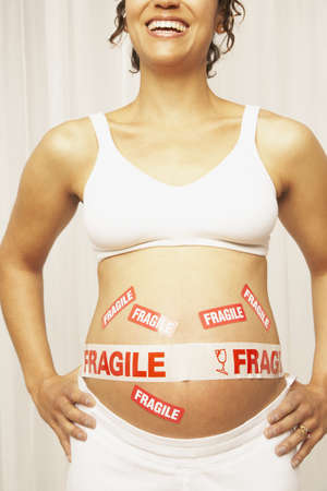 Pregnant Mixed Race woman with fragile tape on belly LANG_EVOIMAGES