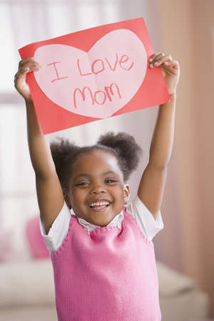 African American girl holding up valentine for mother