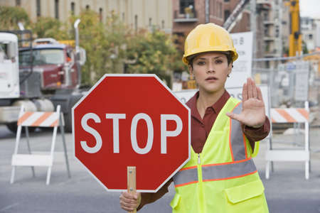 Hispanic female construction worker holding stop sign LANG_EVOIMAGES