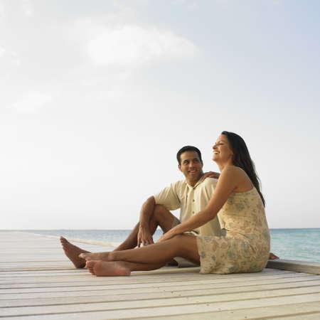 Hispanic couple sitting on pier