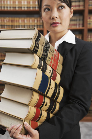 Asian woman carrying stack of library reference books