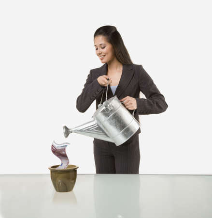 Mixed Race businesswoman watering money in planter