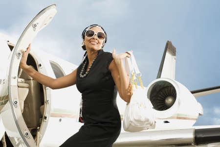 African American woman getting on airplane LANG_EVOIMAGES