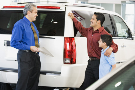Hispanic car salesman talking to father and son