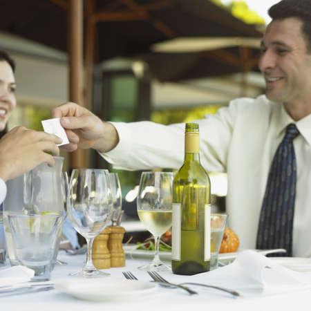 Businessman handing business card over restaurant table