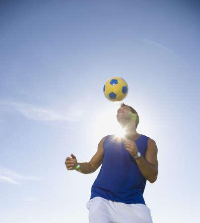 Hispanic man bouncing soccer ball on head LANG_EVOIMAGES