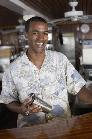 African American male bartender holding shaker