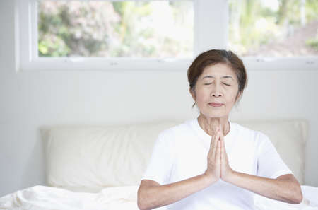 Senior Asian woman meditating on bed LANG_EVOIMAGES