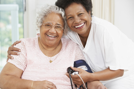 African American mother and adult daughter smiling at each other