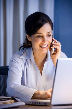 Hispanic businesswoman typing on laptop LANG_EVOIMAGES