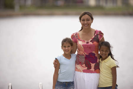Mother and daughters in front of water