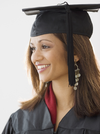 Indian woman wearing graduation cap and gown